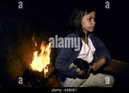 Young girl by a bonfire holds a puppy in her arms at the land invasion at Jardin de Saude Garden of Health Sao Paolo - Stock Photo