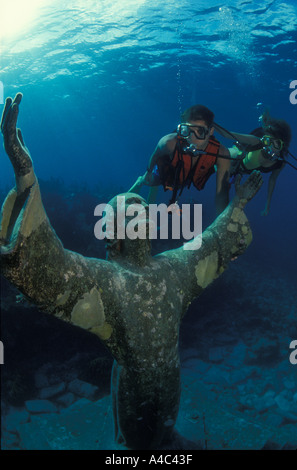 SCUBA DIVERS AND STATUE OF CHRIST OF THE ABYSS FLORIDA KEYS NATIONAL MARINE SANCTUARY KEY LARGO FLORIDA - Stock Photo