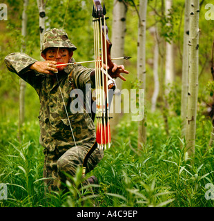 Bow hunter taking aim in a forest setting - Stock Photo