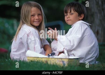 Portrait of little girl and little boy outside in paint shirts. - Stock Photo