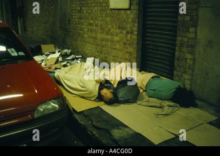 HOMELESS PEOPLE SLEEPING IN A CAR PARK, NEAR KINGS CROSS,  LONDON 1992 - Stock Photo