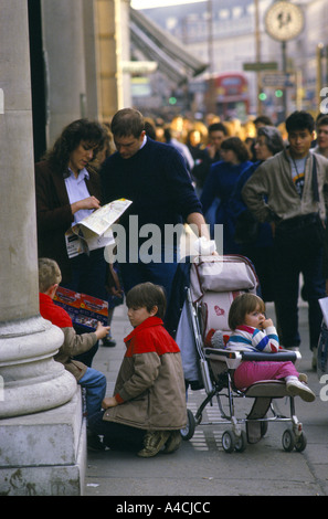 TOURISTS WITH YOUNG CHILDREN CHECKING MAP ON STREET, LONDON, ENGLAND - Stock Photo