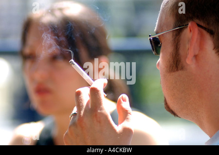 Royalty free photograph of British college university student smoking outside due to smoking ban in London UK - Stock Photo