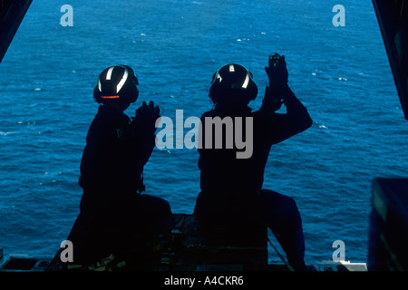 USCG crew of the International Ice Patrol on the loading ramp of the HC130 Hercules prepare to drop weather buoys - Stock Photo