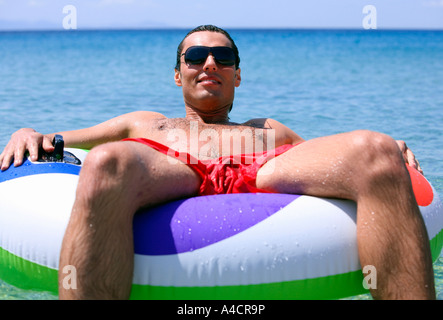 Man in the water on inflatable life ring - Stock Photo