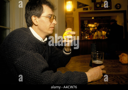 SMOKESTOP' LUNDY ISLAND 1994, A SMOKESTOPPER IN THE MARISCO TAVERN WITH HIS STRESSBALL AND A GLASS OF BEER. - Stock Photo