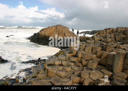 County Antrim Giants Causeway couple climbing on rocks surrounded by heavy surf - Stock Photo
