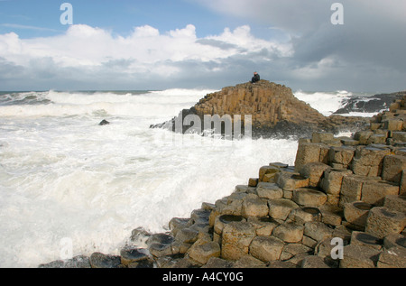 UK County Antrim Giants Causeway couple sat on rocks with waves crashing around - Stock Photo