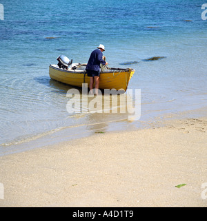 One man and his boat on the island of Bryher in the Scilly Isles western England United Kingdom UK - Stock Photo