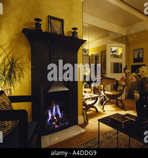 Lighted gas fire in traditional black cast iron fireplace in modern eighties living room - Stock Photo