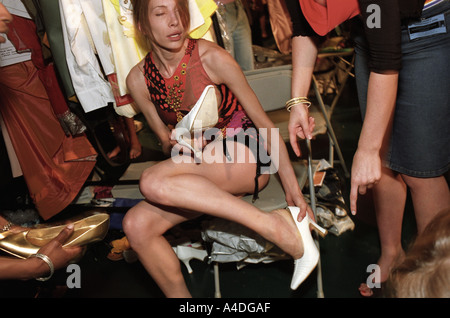 A model trying on shoes backstage at the  Graduate Fashion Shows. Graduate Fashion  Week, London, UK 2001 - Stock Photo