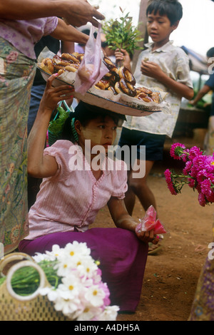 A young girl sells doughnuts from a basket on her head at a village  market. Tenasserim region, Myanmar, Burma - Stock Photo