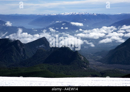 View of the cloud in the valleys around Pucon from the snow covered Villarrica Volcano La Araucania Lake District - Stock Photo