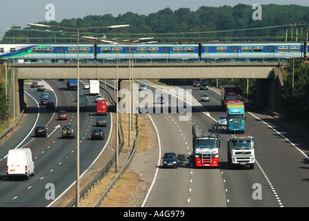 M25 motorway traffic fast train on bridge - Stock Photo