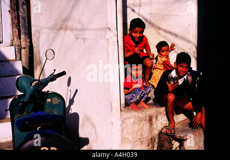 North Indian family dressed mostly in red gathered and sitting at the entrance of a white painted plaster building - Stock Photo