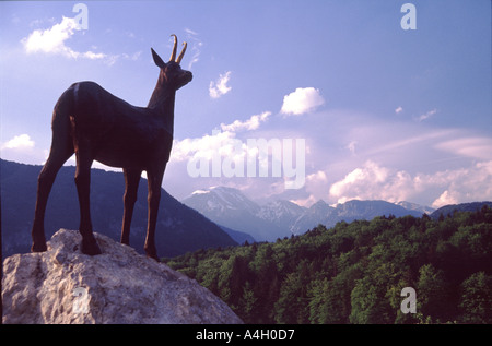 statue of a deer on rock with green hills and white topped mountains in distance Lake Bohinj Slovenia - Stock Photo