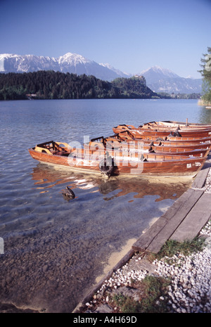 Rowingboats on lake Bled at sunset with mountains and castle in the distance  - Stock Photo