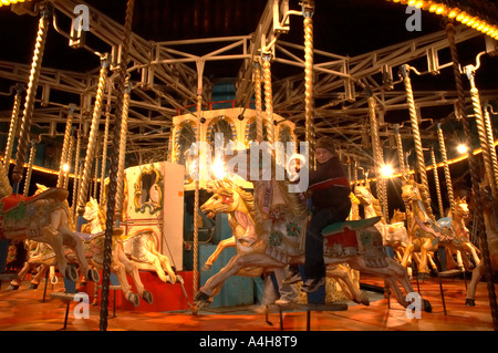 Young Boy on Carousel Horses in Evening Barry Island Pleasure Park Vale of Glamorgan South Wales - Stock Photo