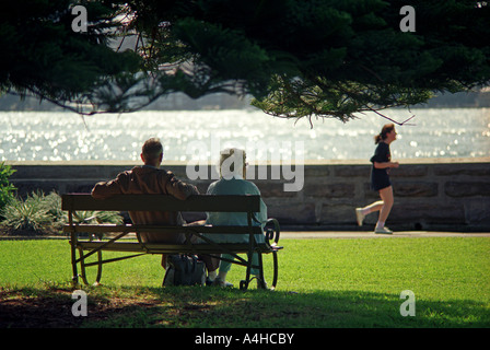 Jogging, An elderly couple watch a young jogger in the park, Sydney, Australia - Stock Photo