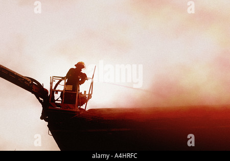 Fireman in cradle on cherry picker spraying fire in rooftop with water from hose - Stock Photo