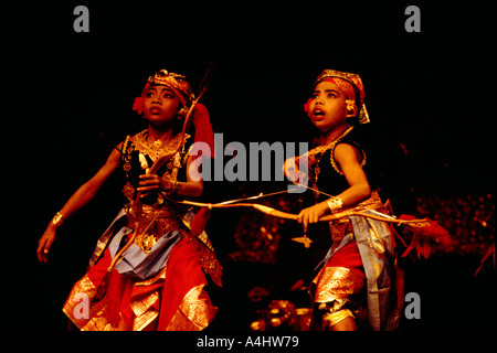 Young Balinese Children shooting Bow and Arrow in Archery Dance Performance and wearing Traditional Costume from - Stock Photo