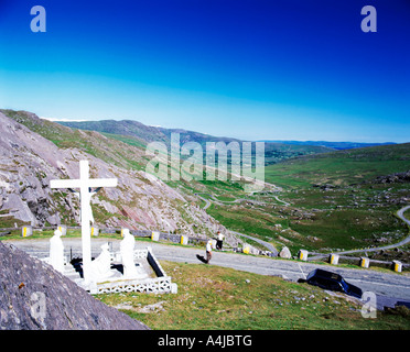 tall religious crucifix stands on top of mountain looking down on the valley below - Stock Photo