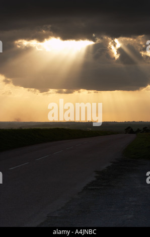 Shafts of sunlight breaking through a dark moody stormy cloudy sky - Stock Photo
