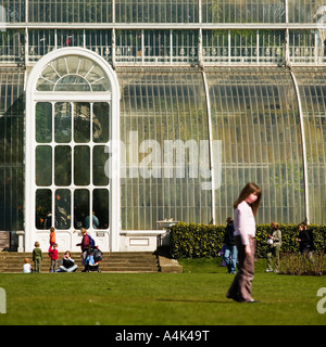 family playing on grass outside the Great Palm House Kew Garden - Stock Photo
