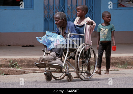 Children pushing a wheelchair with a handicapped relative to beg in the streets of Moshi, Tanzania - Stock Photo