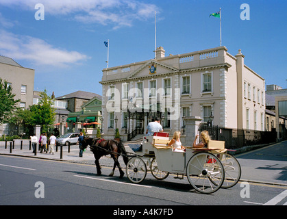 A tourist horse carriage passes the home of the Lord Mayor of Dublin the Mansion House on Dawson Street - Stock Photo