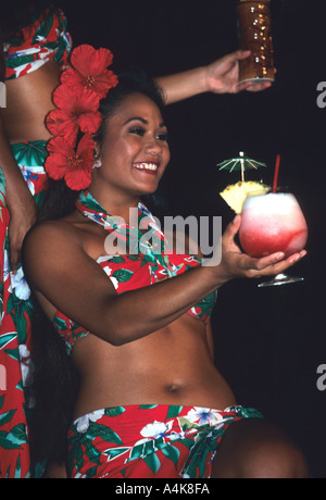 beautiful young dancer offers a welcome coconut based drink to tourists at a show in Honolulu Hawaii USA - Stock Photo
