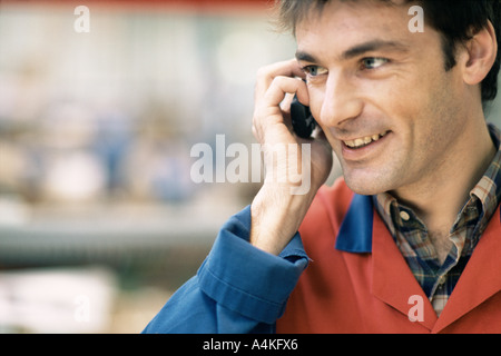 Manual worker using cell phone - Stock Photo