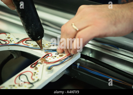Affixing electrical wires with glue gun - Stock Photo