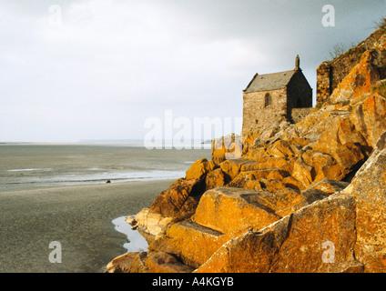 Stone house on rocks overlooking beach - Stock Photo