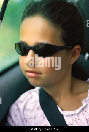 Girl in car wearing seat belt - Stock Photo