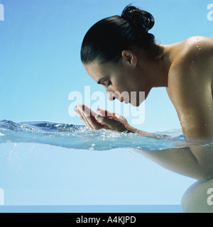 Woman kneeling in water, cupping hands to face - Stock Photo