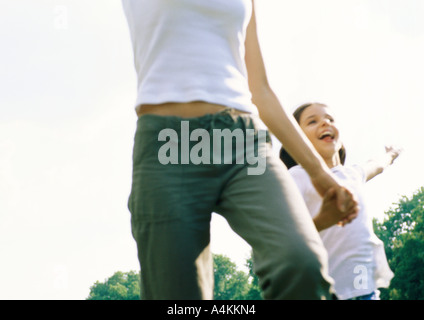Woman and child holding hands and running outside - Stock Photo
