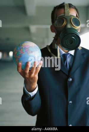 Businessman holding globe up in hand, wearing gas mask over face - Stock Photo