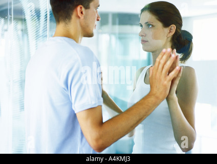 Couple, face to face, putting hands together on either side of glass wall - Stock Photo
