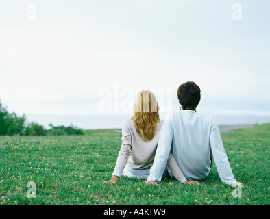 Young man and young woman sitting side by side on grass, propped up with hands, rear view - Stock Photo