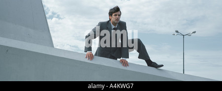 Man in suit climbing over low concrete wall - Stock Photo