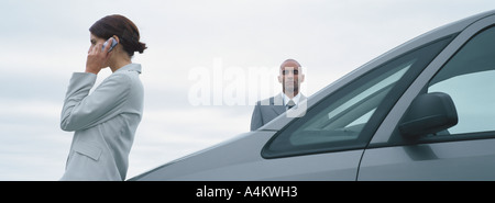 Woman and man in suits standing near car, man looking at camera, woman talking on cell phone - Stock Photo