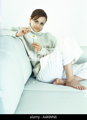 Woman sitting with knee up on sofa, plucking petals from daisy - Stock Photo