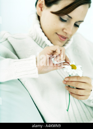 Woman plucking petals from daisy, looking down, close-up - Stock Photo