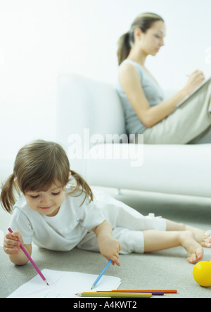 Little girl lying on floor coloring, young woman sitting behind her on couch writing with knees up - Stock Photo