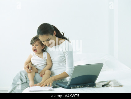 Woman sitting on bed with little girl on lap crying, looking down at paper - Stock Photo