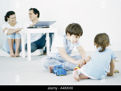 Boy and girl playing on floor, parents using laptop in background - Stock Photo