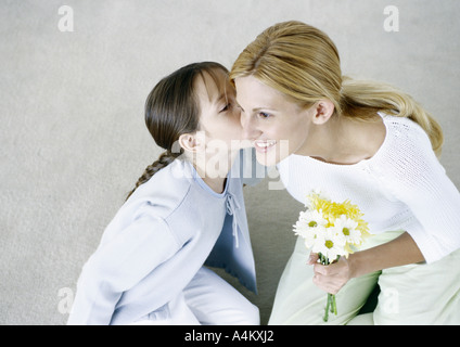 Woman holding bouquet of flowers, girl kissing her cheek - Stock Photo