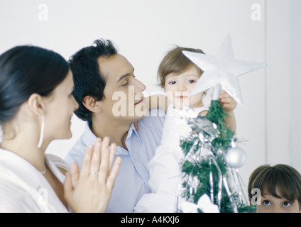 Little girl in fathers arms touching star on Christmas tree next to mother and brother - Stock Photo