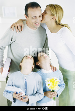 Woman kissing man on cheek, girl and boy looking up with heads back - Stock Photo
